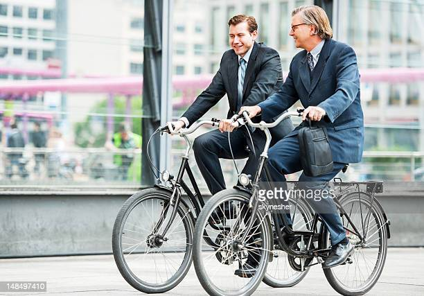 Two businesspeople riding bicycles.