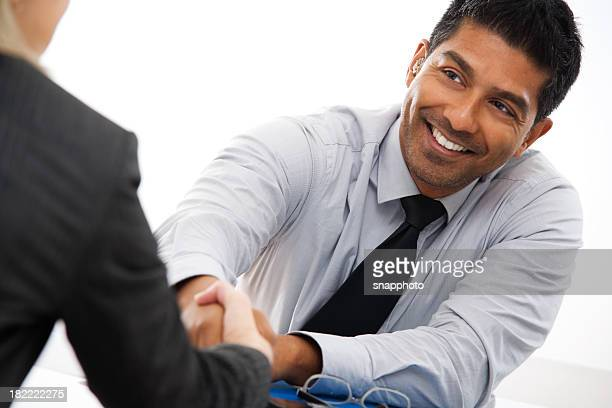 Two businesspeople shaking hands across a desk