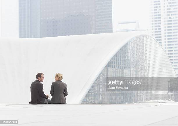 Two businesspeople sitting outdoors on step
