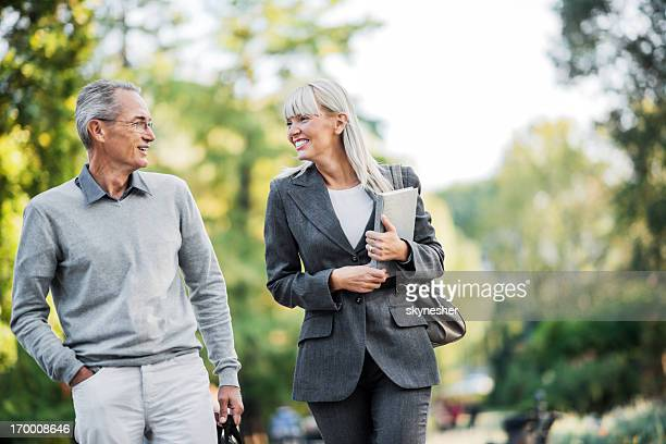 Two businesspeople taking a walk in park.