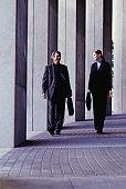 Two businesspeople walking beside a colonnade, outside