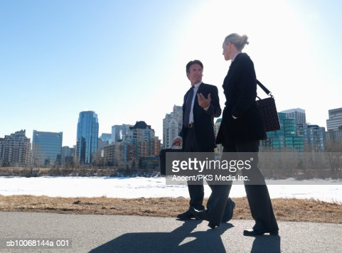 Two businesspeople walking down street, snow covered river and skyline in background : Stock Photo