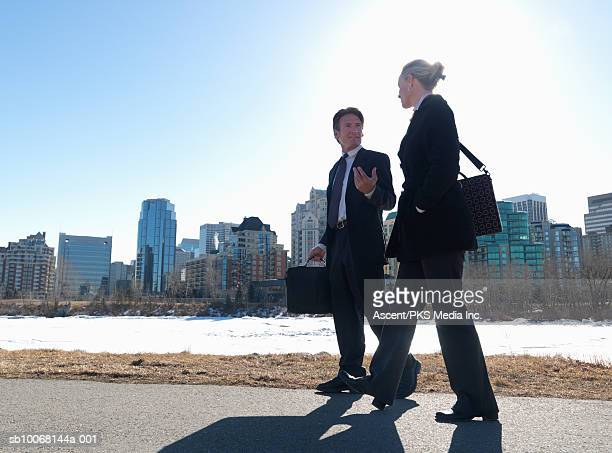 Two businesspeople walking down street, snow covered river and skyline in background