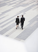 Two Businesspeople Walking through Plaza