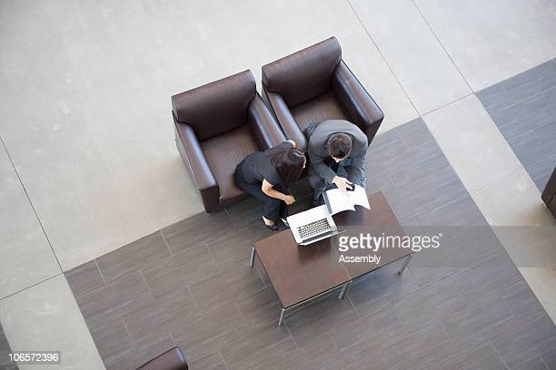 Two businesspeople working on laptop in foyer