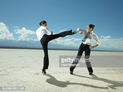 Two businesswoman fighting in desert landscape : Stock Photo