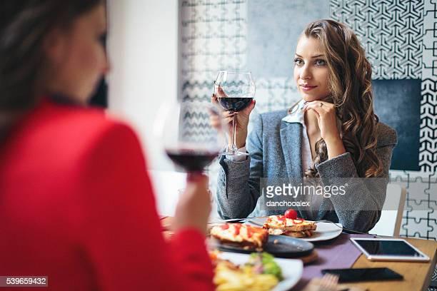 Due donna d'affari avendo un bicchiere di vino e pranzo