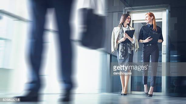 Two businesswoman walking and talking