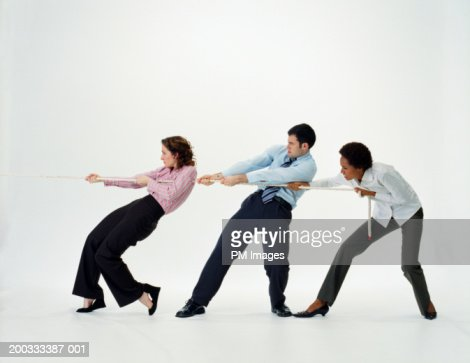 Two businesswomen and businessman pulling rope, side view