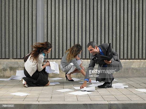 Two businesswomen and one businessman trying to recover papers blowing about pavement, Alicante, Spain,