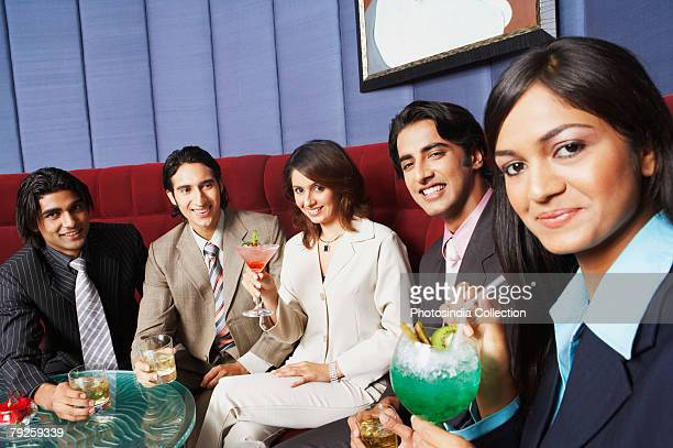 Two businesswomen and three businessmen sitting on a couch and holding glasses