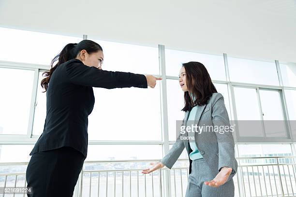 Dos mujeres empresarias argumentando en oficina