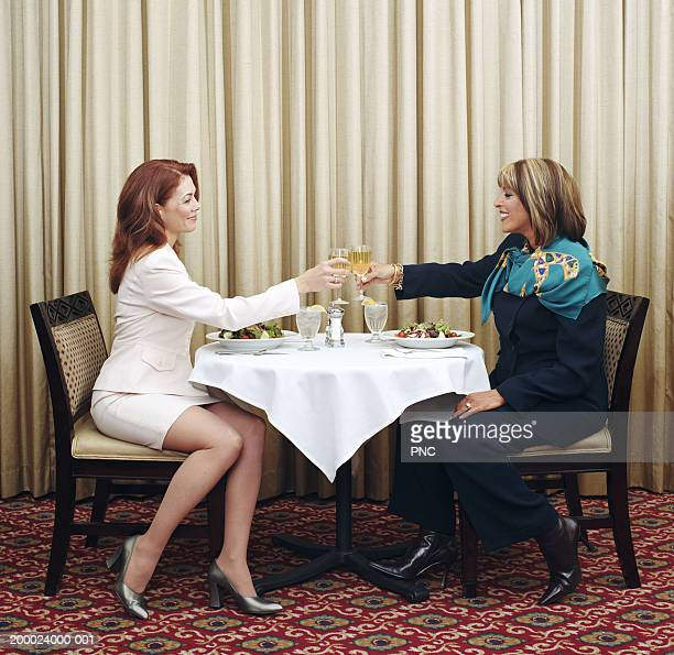 Two businesswomen at lunch, toasting with white wine