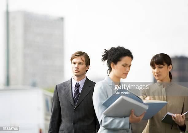Two businesswomen discussing file, businessman passing by in background