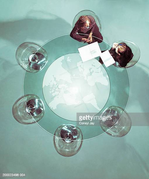 Two businesswomen in discussion at glass table, overhead view