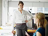 Two businesswomen in discussion in workstation