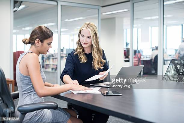 Two businesswomen in modern office looking at documents