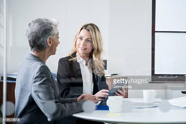 Two businesswomen in modern office with tablet