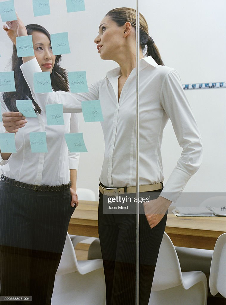Two businesswomen in office discussing memo notes on glass wall : Stock Photo