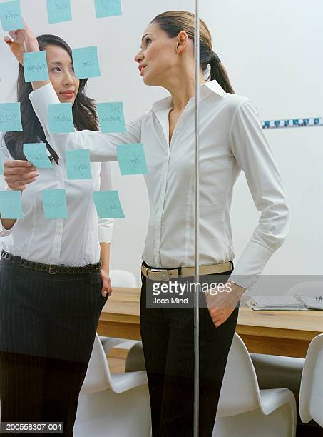 Two businesswomen in office discussing memo notes on glass wall