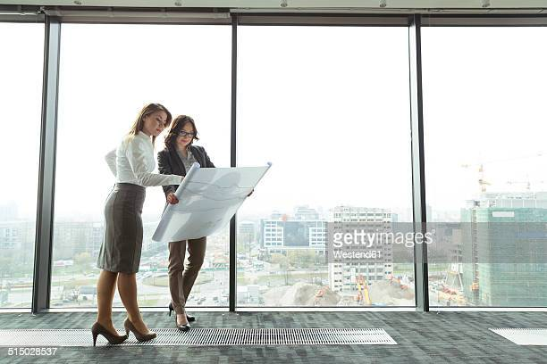 Two businesswomen in office looking at blueprint
