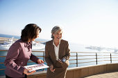 Two businesswomen laughing by sea, one holding electronic organiser