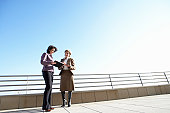 Two businesswomen looking at folder outdoors, low angle view