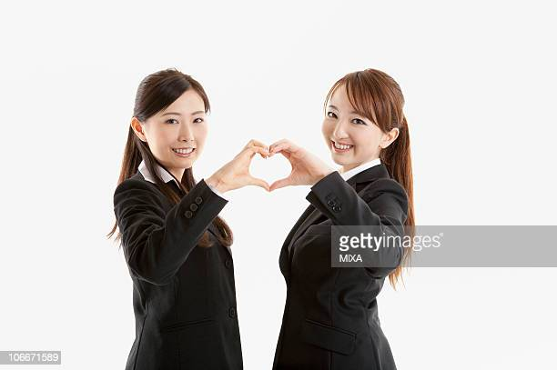 Two businesswomen making heart shape with hands