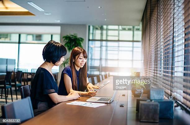 Two businesswomen on meeting using online data