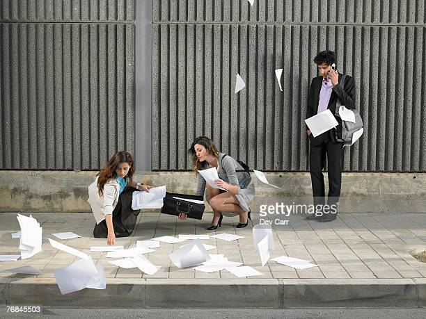 Two businesswomen picking up papers blowing about pavement while a young man looks on, talking on the phone,