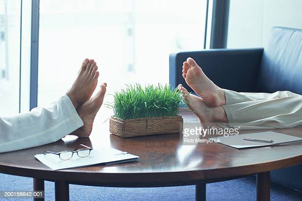 Two businesswomen resting feet on coffee table, low section, side view