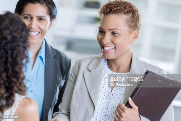 Two businesswomen shake hands with interviewee