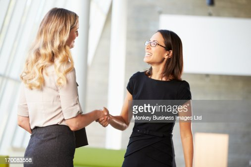 Two Businesswomen Shaking Hands In Modern Office : Stock Photo