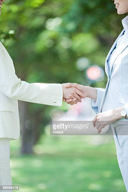 Two businesswomen shaking hands outside, side view