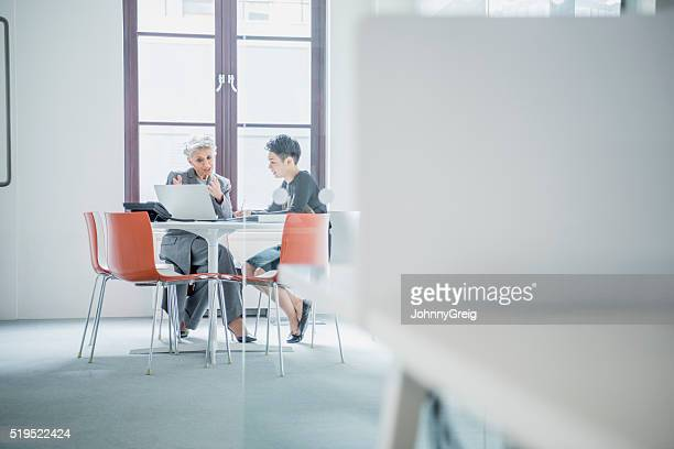 Two businesswomen sitting at table in modern office