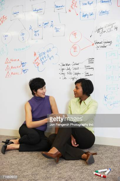 Two businesswomen sitting on floor in front of whiteboard wall