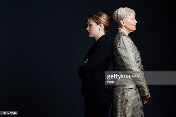 Two Businesswomen Standing Back to Back