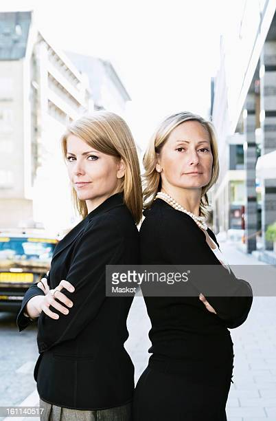 Two businesswomen standing back-to-back