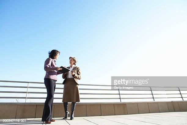 Two businesswomen standing outdoors, low angle view
