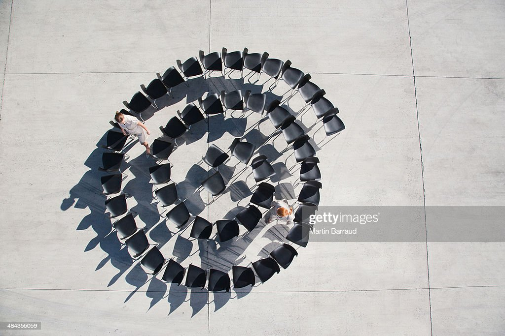 Two businesswomen standing with spiral of office chairs : Stock Photo