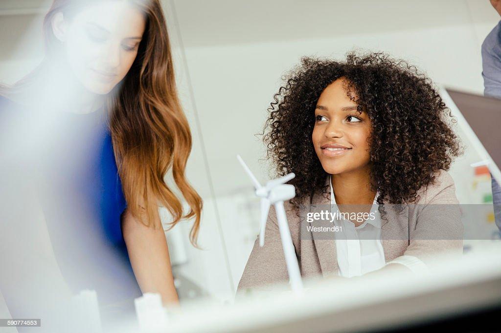 Two businesswomen talking about wind turbine model