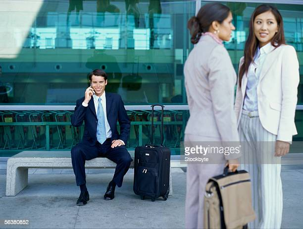 two businesswomen talking and a businessman holding a mobile phone behind them