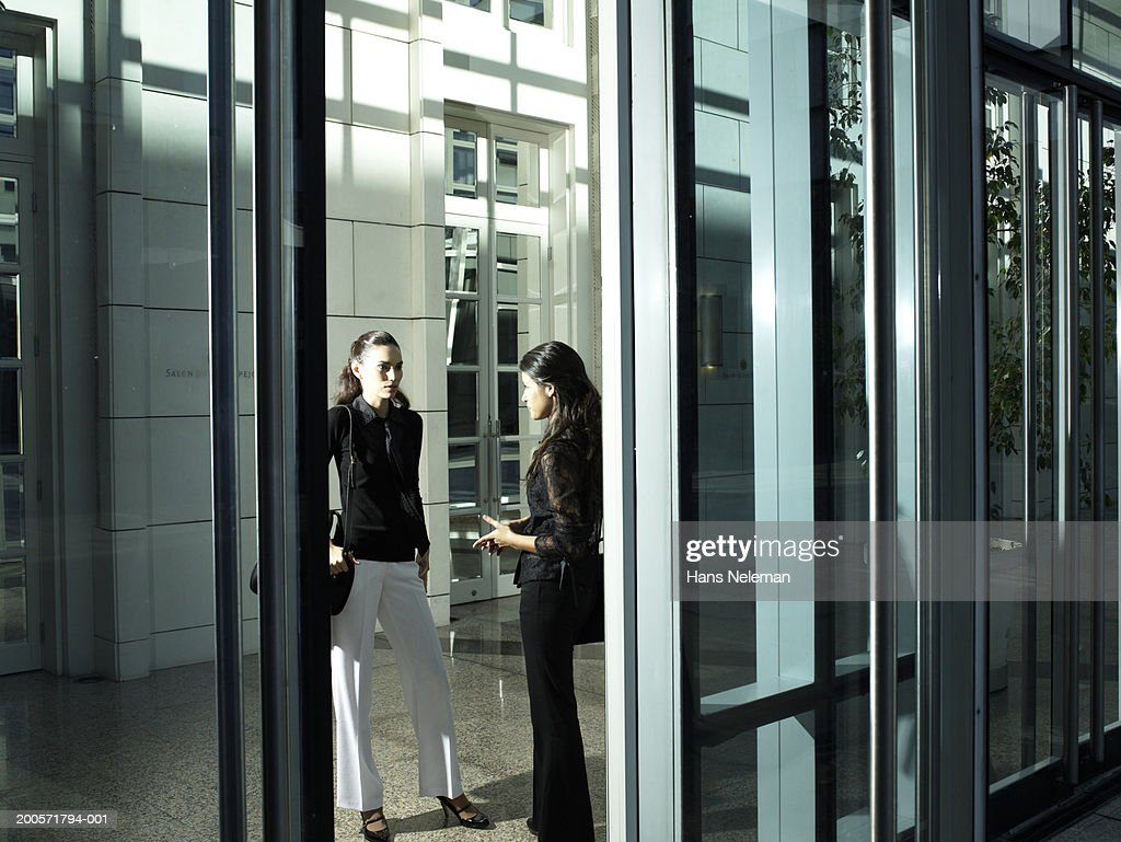 Office Foyer Images : Two businesswomen talking in office foyer stock photo