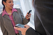 Two businesswomen text messaging on mobile phones
