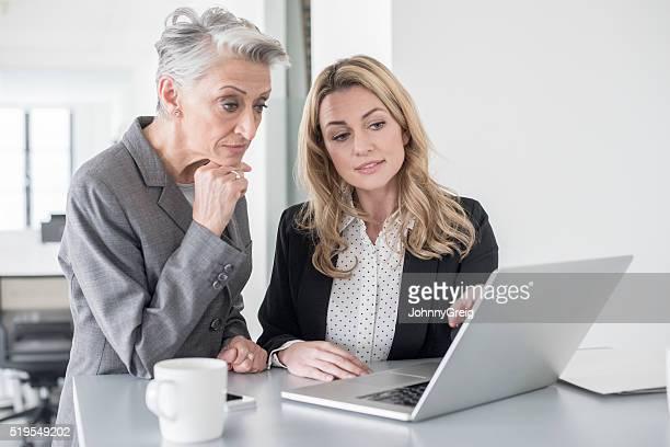 ZWEI GESCHÄFTSFRAUEN mit Laptop, die Konzentration auf dem Bildschirm