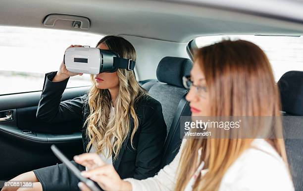 Two businesswomen with VR glasses and digital tablet in car