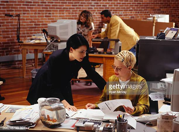 Two businesswomen working and talking in office