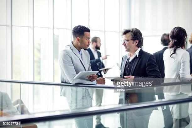 Deux busuinessmen avoir une conversation décontractée dans le Hall