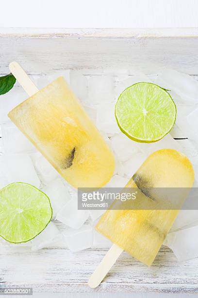 Two caipirinha ice lollies, ice cubes and slices of lime on white wood