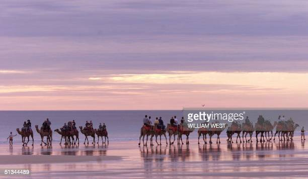 Two camel trains pass one another as they carry tourists down Broome's famous Cable Beach 23 May 2000 as Broome recovers from a cyclone at the start...